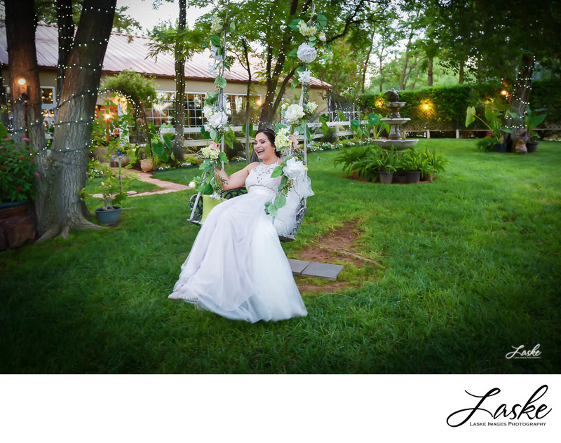 Bride Sits on Wooden Swing Hanging From Tree Laughing