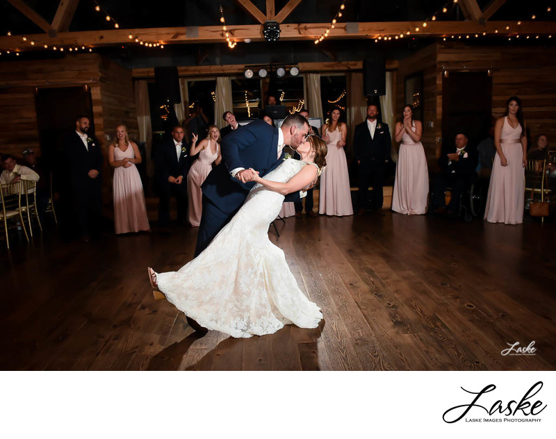 Groom Leans Bride Back to Kiss Her During First Dance