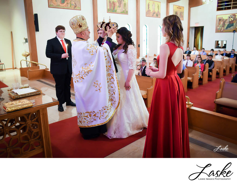 Priest places crown on Bride during wedding ceremony