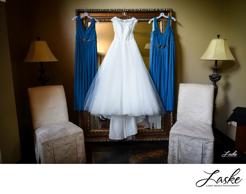 White Wedding Dress with Blue Bridesmaids Dresses Hang on Mirror