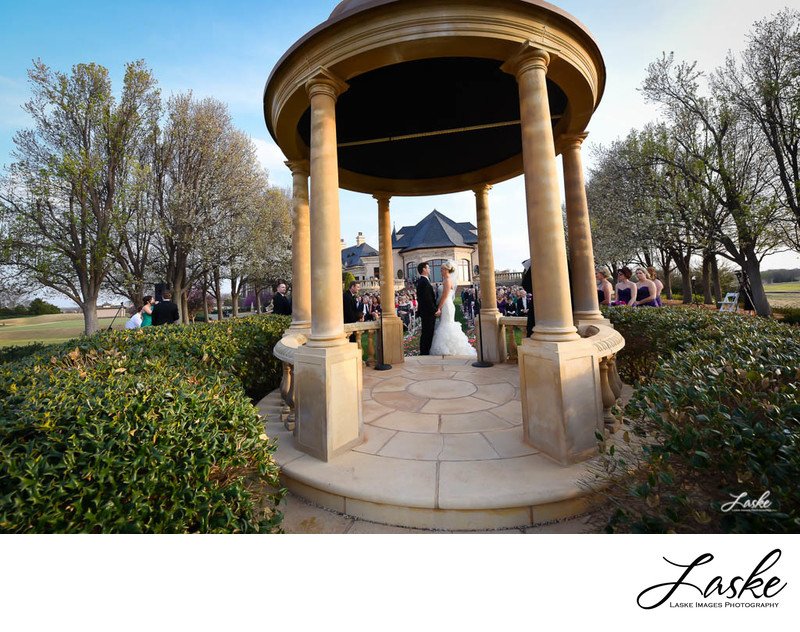 The Bride and Groom facing each other Holding Hands in the Gazebo in front of wedding guests at Gaillardia Country Club in Oklahoma City, Oklahoma.