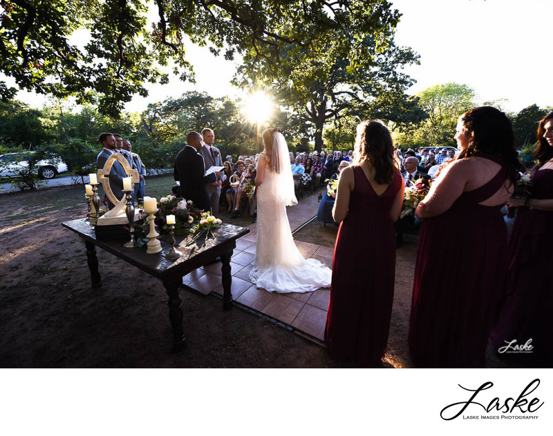 Bride and Groom stand in front of their wedding guests at sunset
