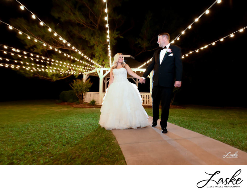 Bride and Groom Walk Down Sidewalk Under Party Lights at Wings Event Center