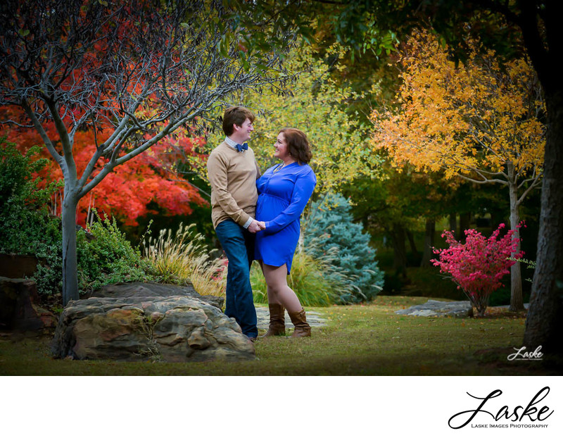 Couple Looks at Each Other During Outdoor Fall Session with Beautiful Trees
