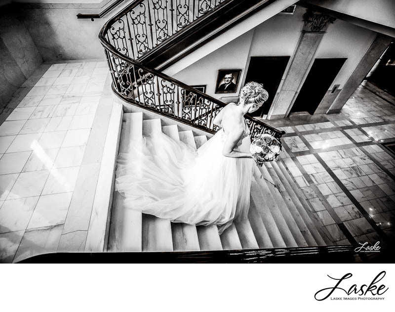 Bride Runs Down the Stairs in Wedding Gown Holding Bouquet