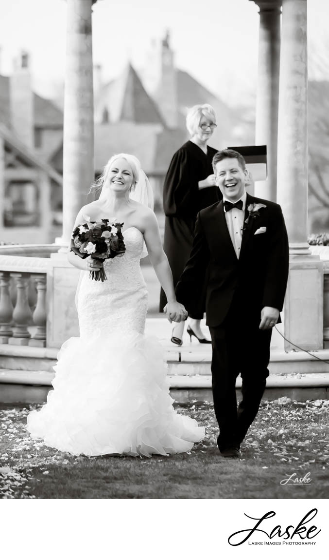 Bride and Groom Laughing as they Walk Out After Wedding