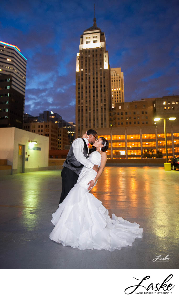 Groom Tips Bride Back and Kisses Her on the Rooftop Surrounded by Tall Buildings in Oklahoma City
