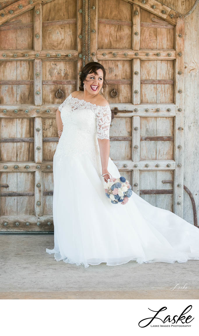 Bride Laughing Outside Doors With Bouquet