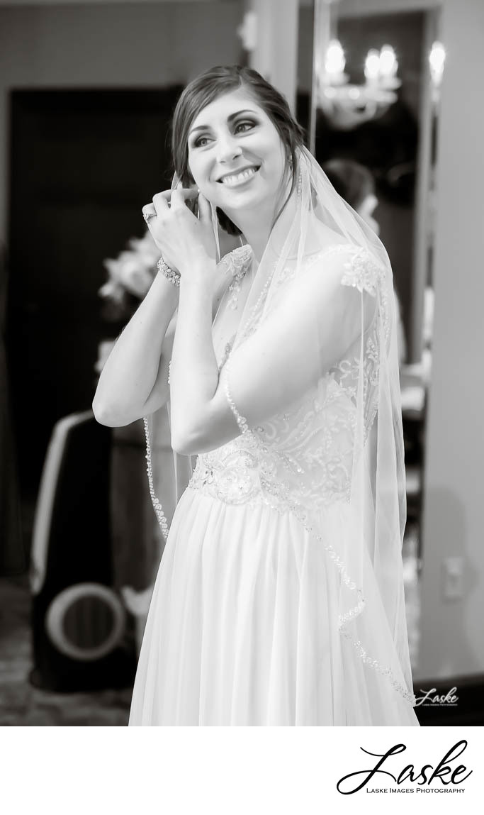 Black and White Picture of Smiling Bride Putting in Earrings on Her Wedding Day