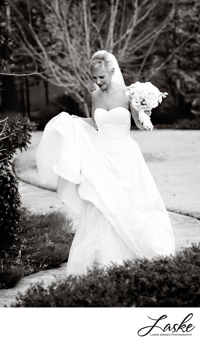 Black and White of Bride Walking Through Gardens