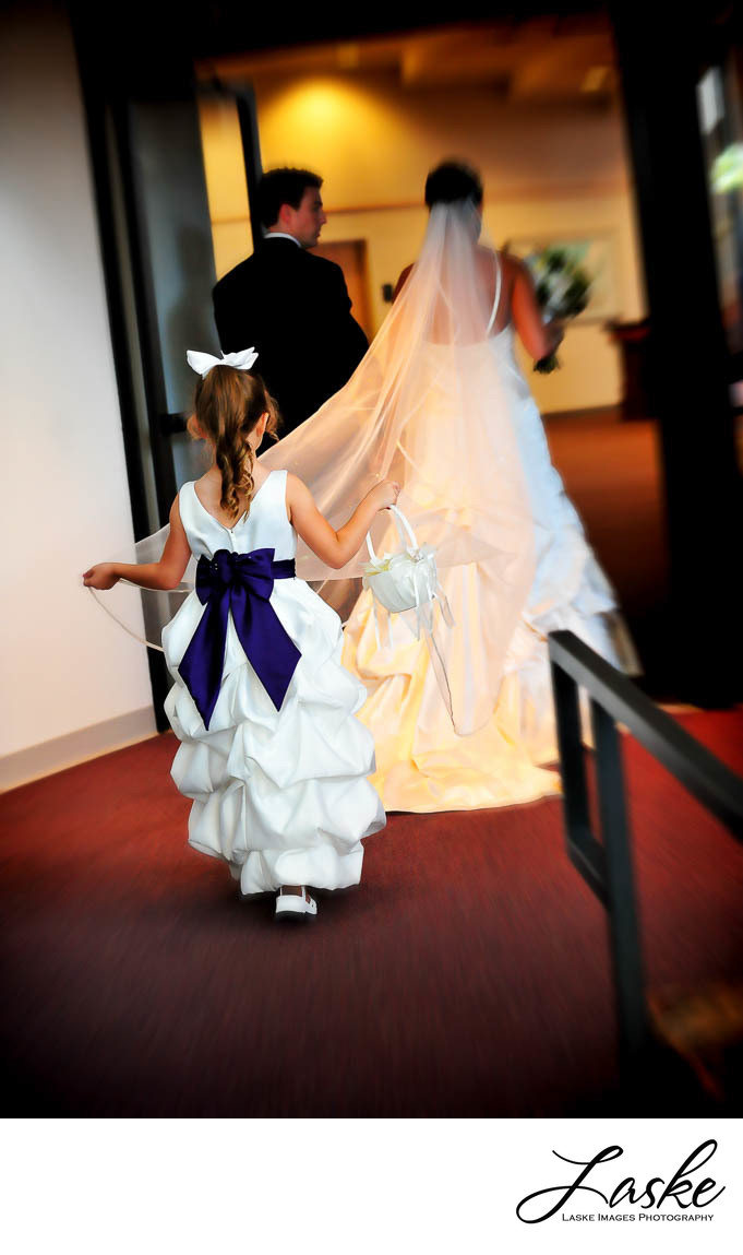 The flowergirl holds the Bride's veil as the couple walks through the venue