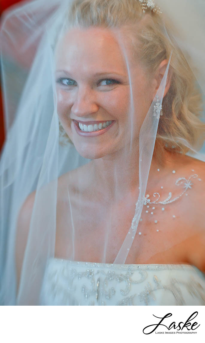 Smiling Bride Showcases the Details in Her Veil
