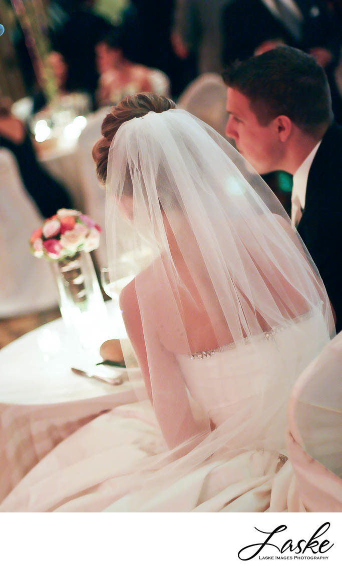 Bride and Groom Sitting at Table in Wedding Reception