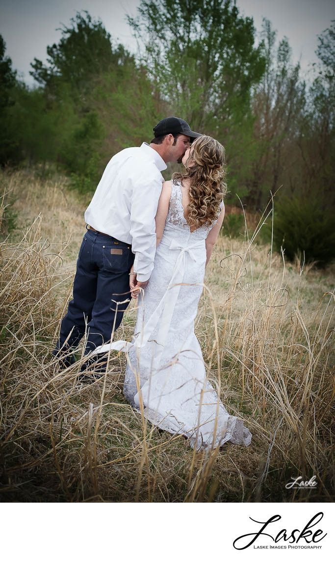 Bride and Groom Kiss in a Wooded Field