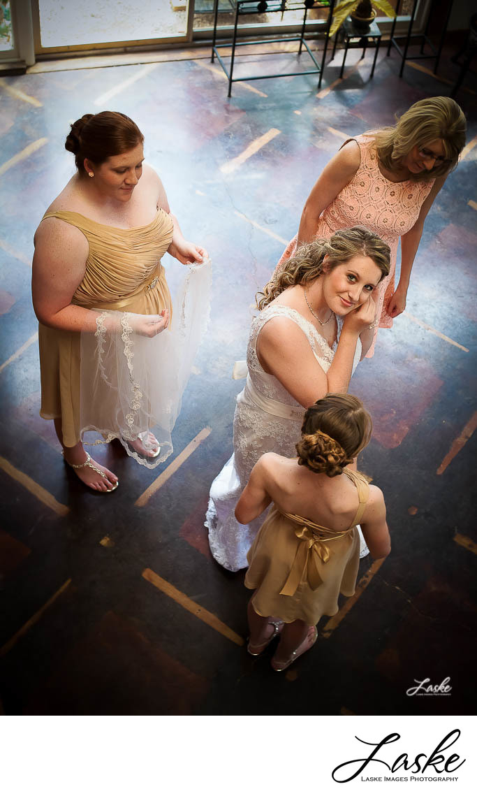 Bride Looks Up at Photographer as She Puts on Earrings