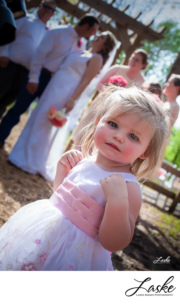 Flower Girl Stops to Look at Photographer with Wedding Party in the Background