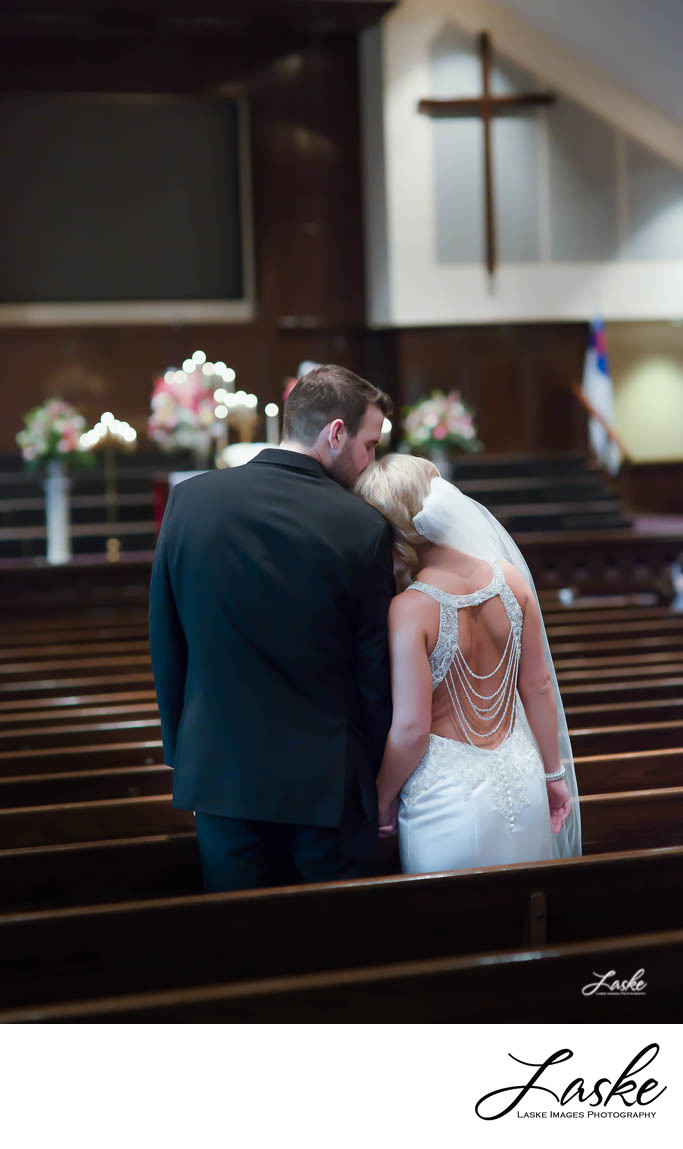 Bride rests her head on her Grooms shoulder as he kisses her on the head