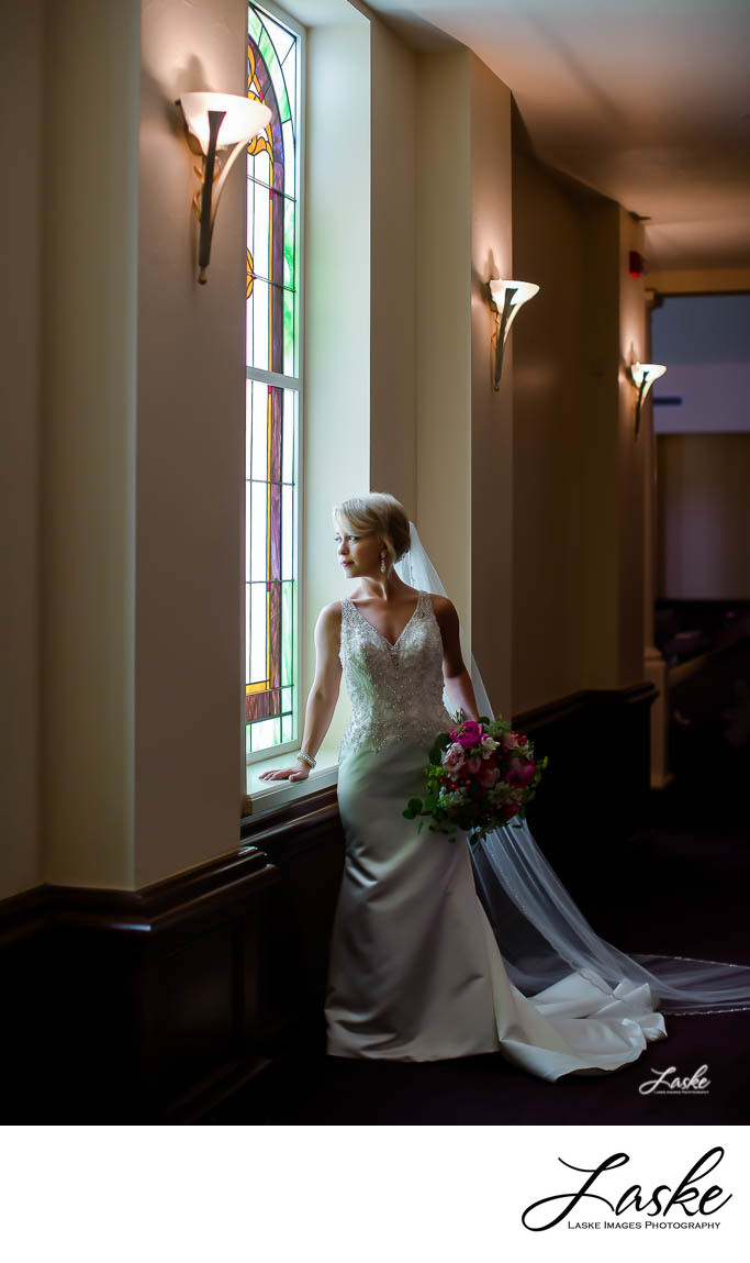 Bride Looks Out Stained Glass Window with Bouquet in Hand