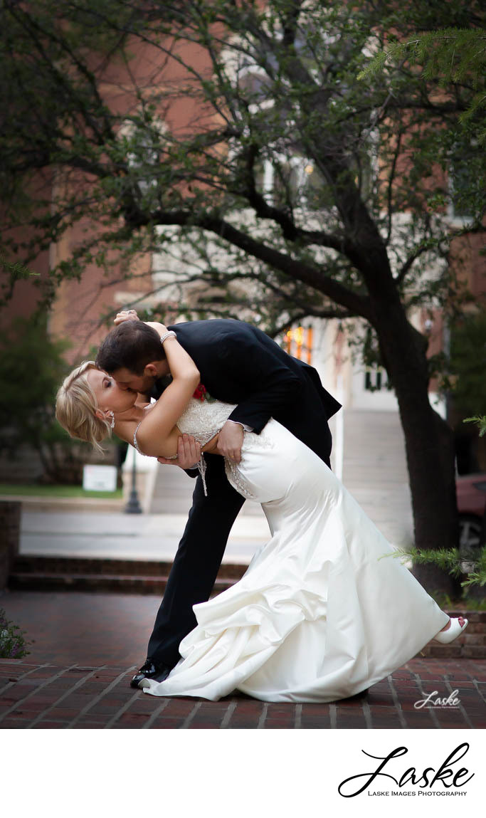 Groom Dips Bride and Kisses Her Outside College Buildings
