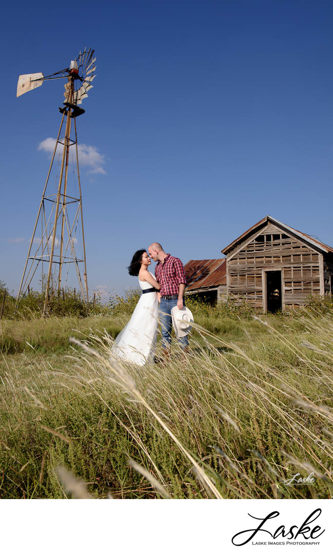 Groom and Bride Face to Face in Field with Barn and Windmill