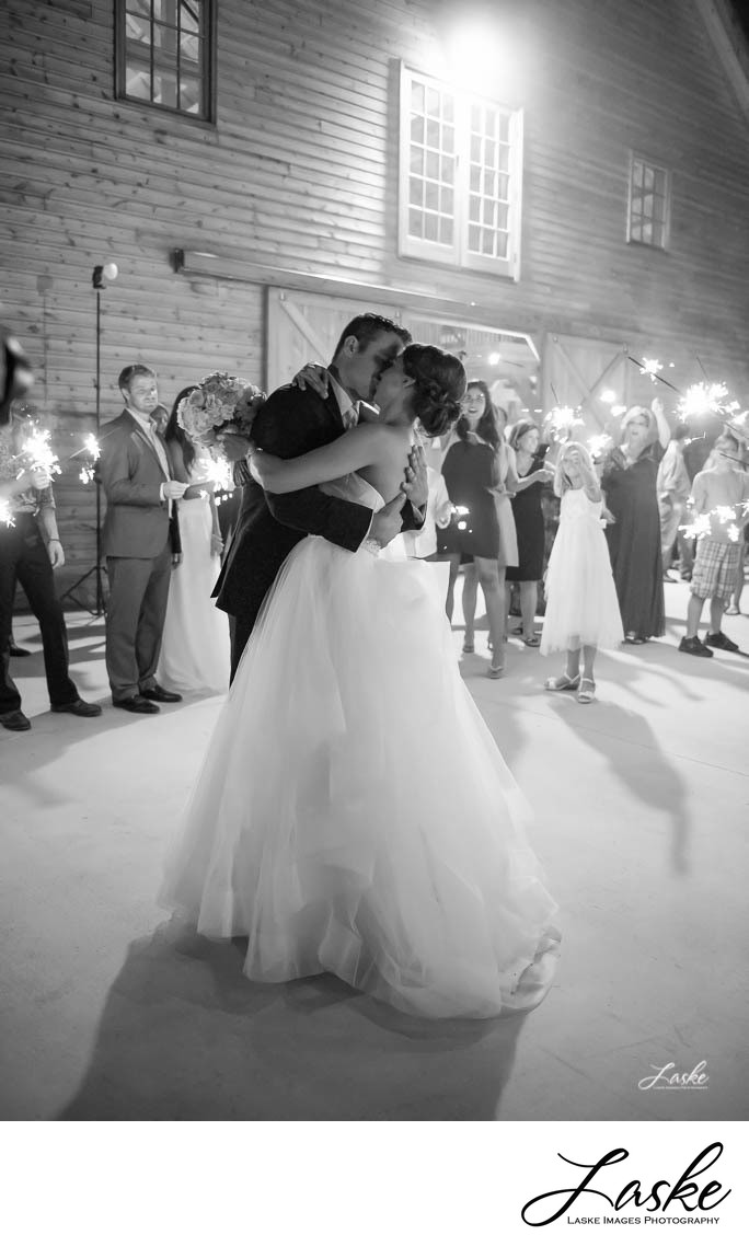 Bride and Groom stop to kiss sounded by wedding guests waving sparklers outside the McGranahan Barn in Piedmont, Oklahoma.