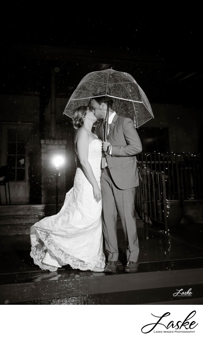 Bride and Groom Kiss Under Umbrella Outside