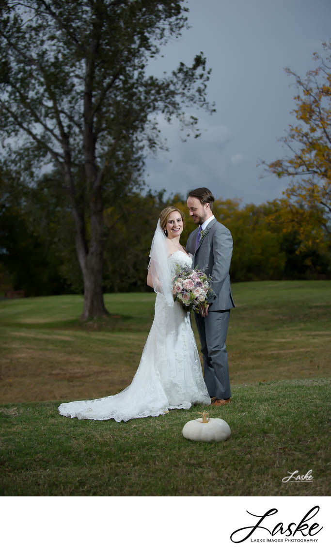 Bride and Groom standing in the grass with Pumpkin