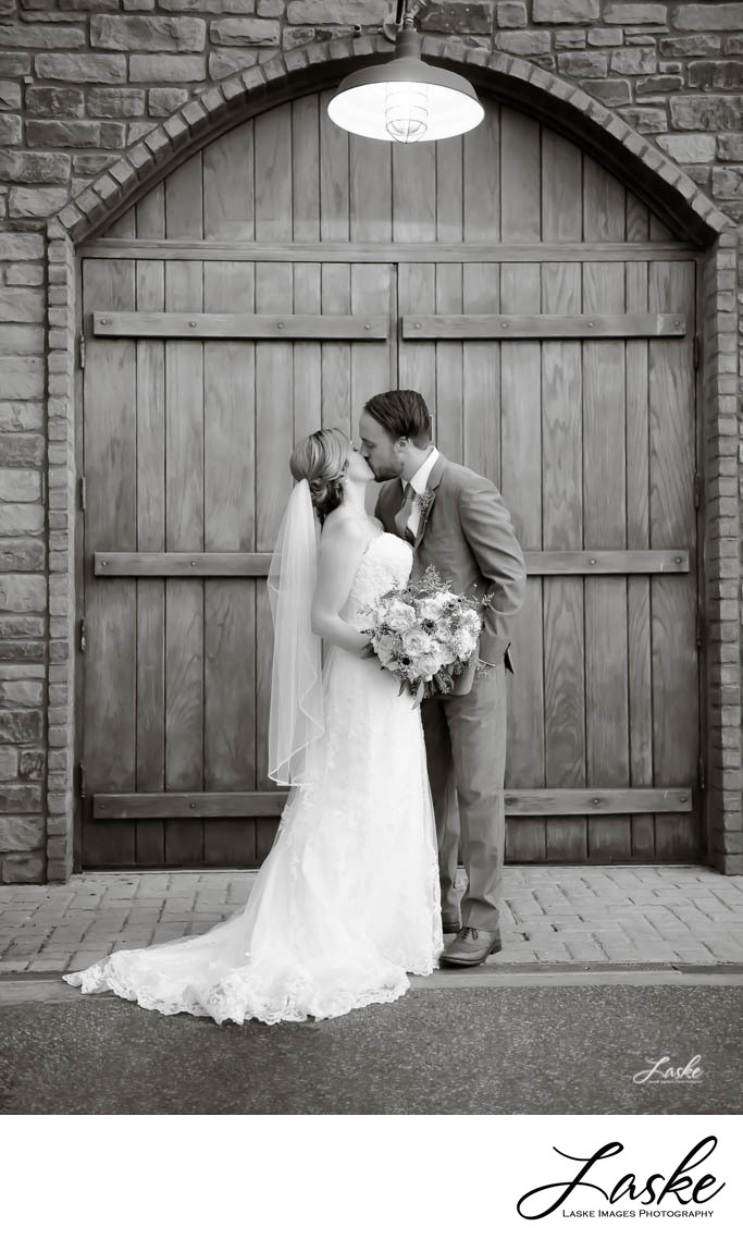 Couple kisses on their wedding day outside doors of vineyard