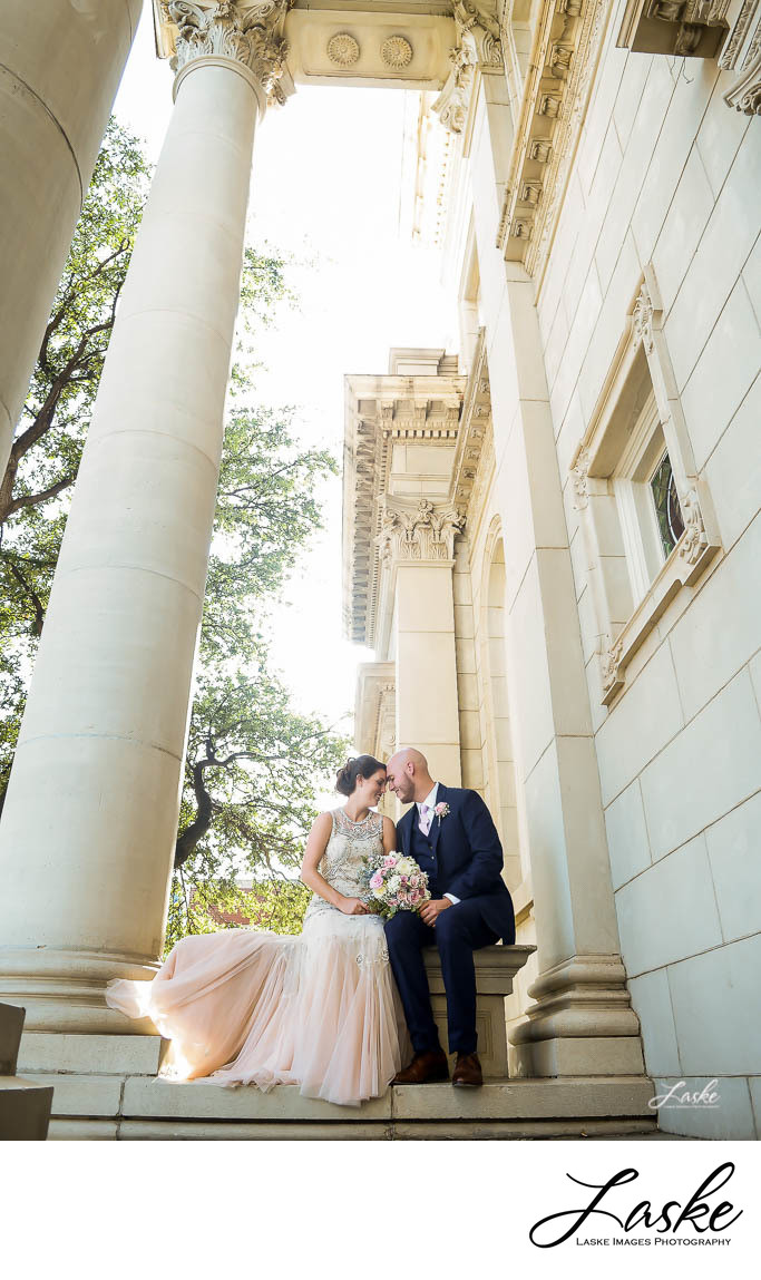 OKC Wedding Photographers Bride and Groom Forehead to Forehead as they Sit on Ledge of Building