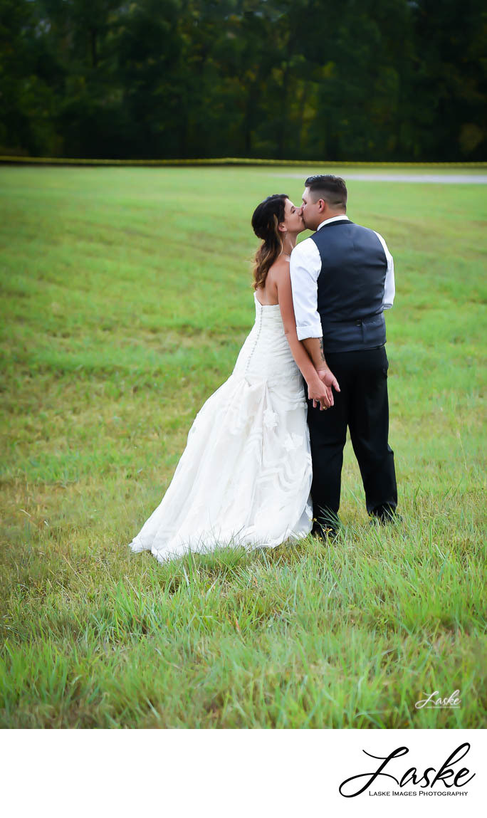 Bride Leans Over to Kiss Groom as they Walk through Field