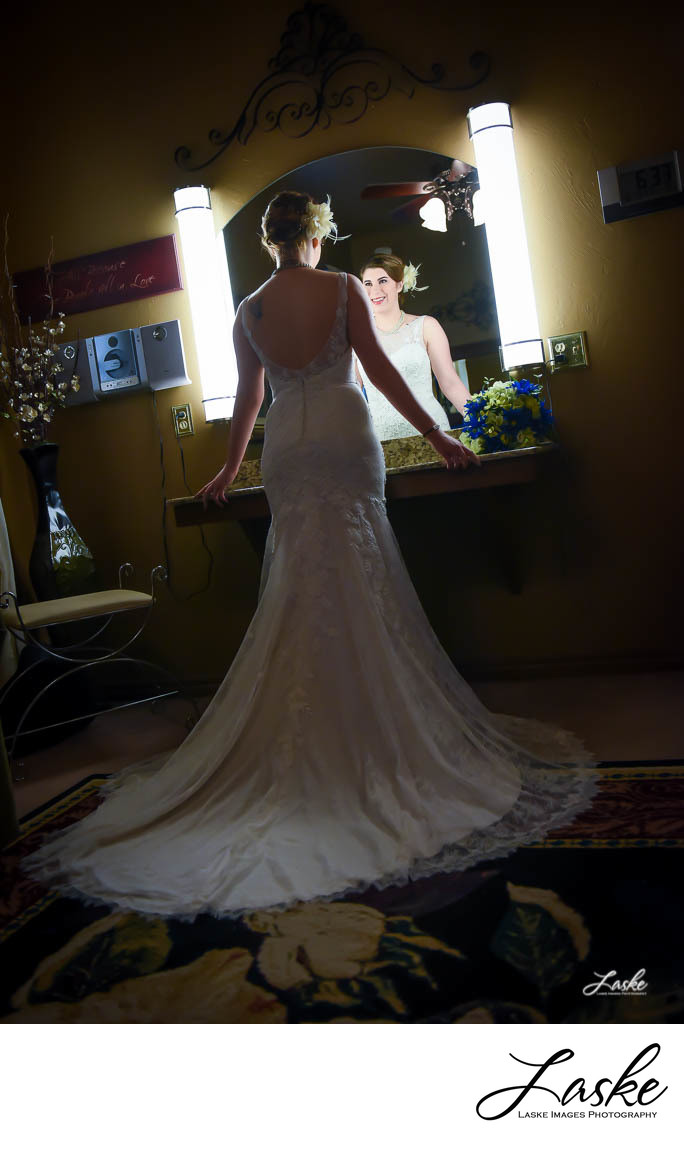 Bride stands in front of a lit Mirror on her Wedding Day