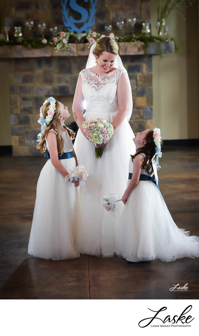 Bride looks down at her little Flower Girls who Smile up at Her