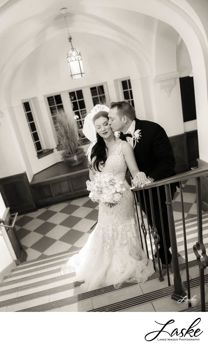 Groom kisses his Bride on the stairwell of the wedding venue