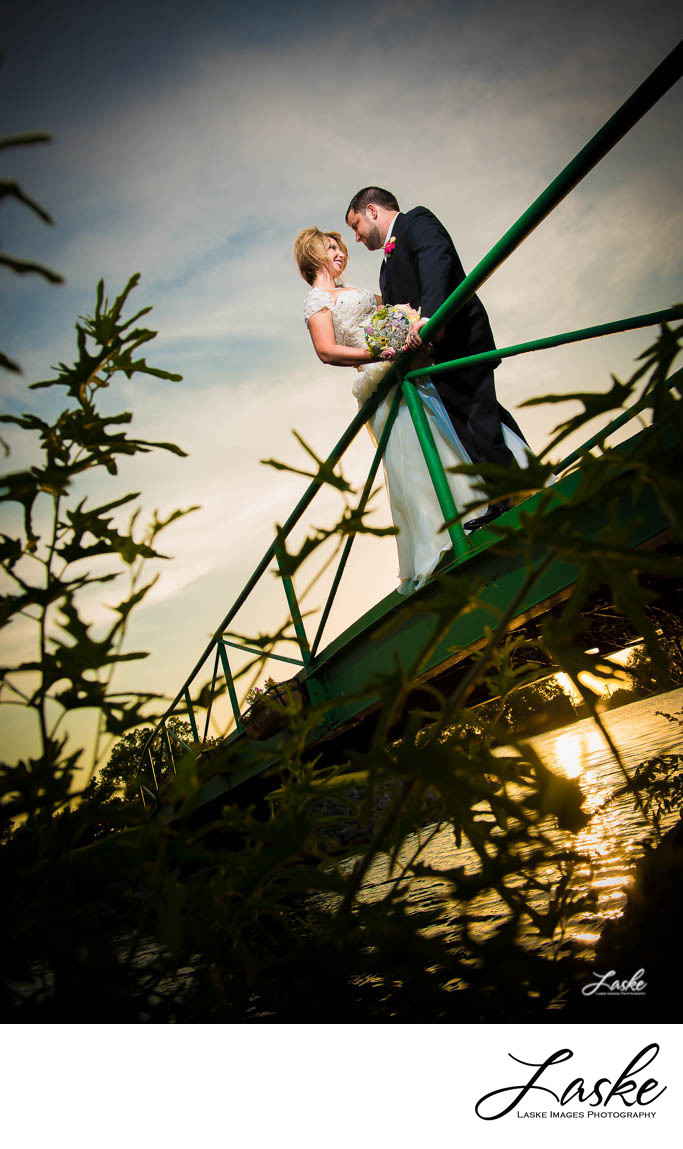 Photographers in OKC ShootBride and Groom Stand Facing On Bridge During Sunset