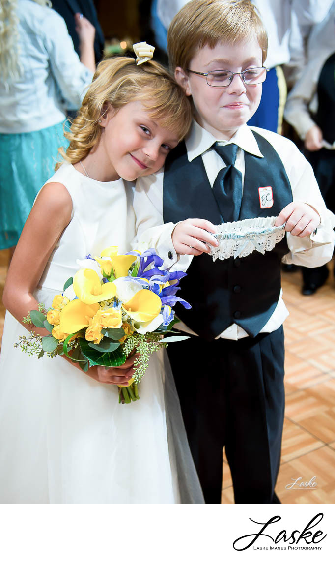 Ring Bearer Blushes Holding Garter and Flower Girl Catches Bouquet