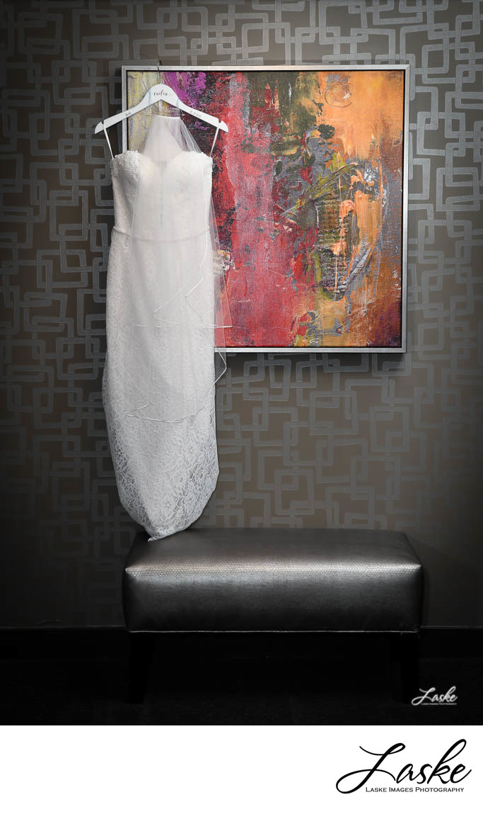 Beautiful Wedding Dress Hanging On a Colorful Abstract Painting