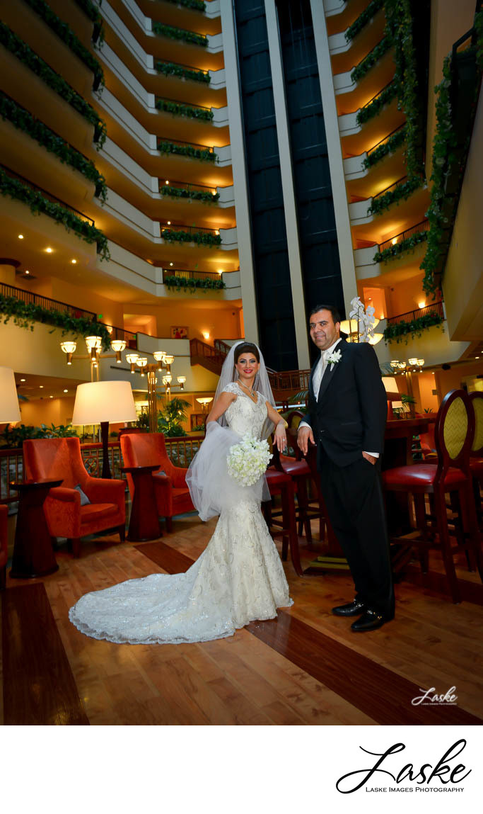 Bride and Groom Smile for a portrait in the sitting area of the Embassy Suites Hotel in Oklahoma City, Oklahoma.