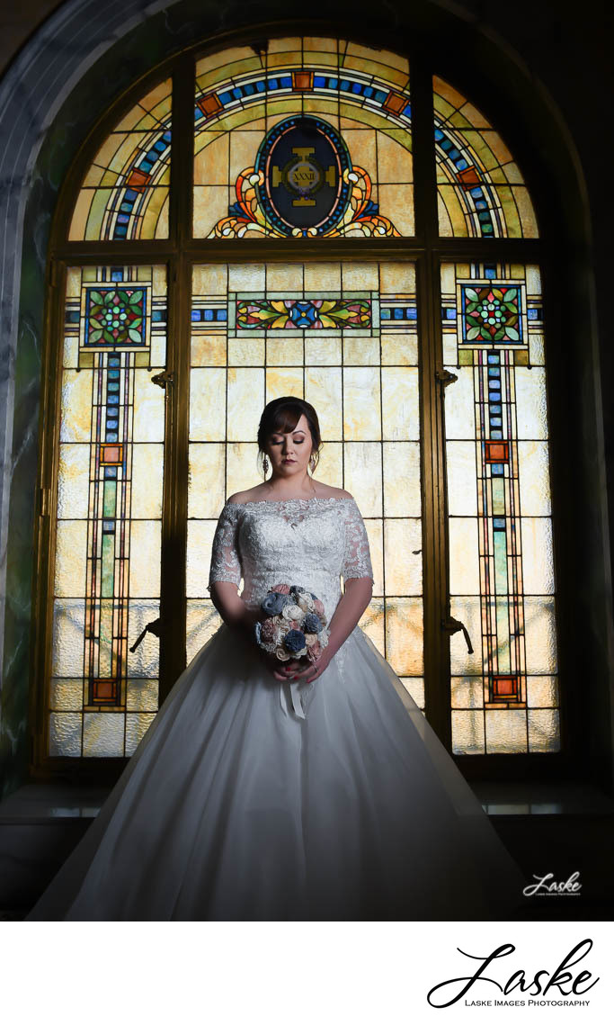 Bride Standing In Front of Stained Glass Eyes Closed