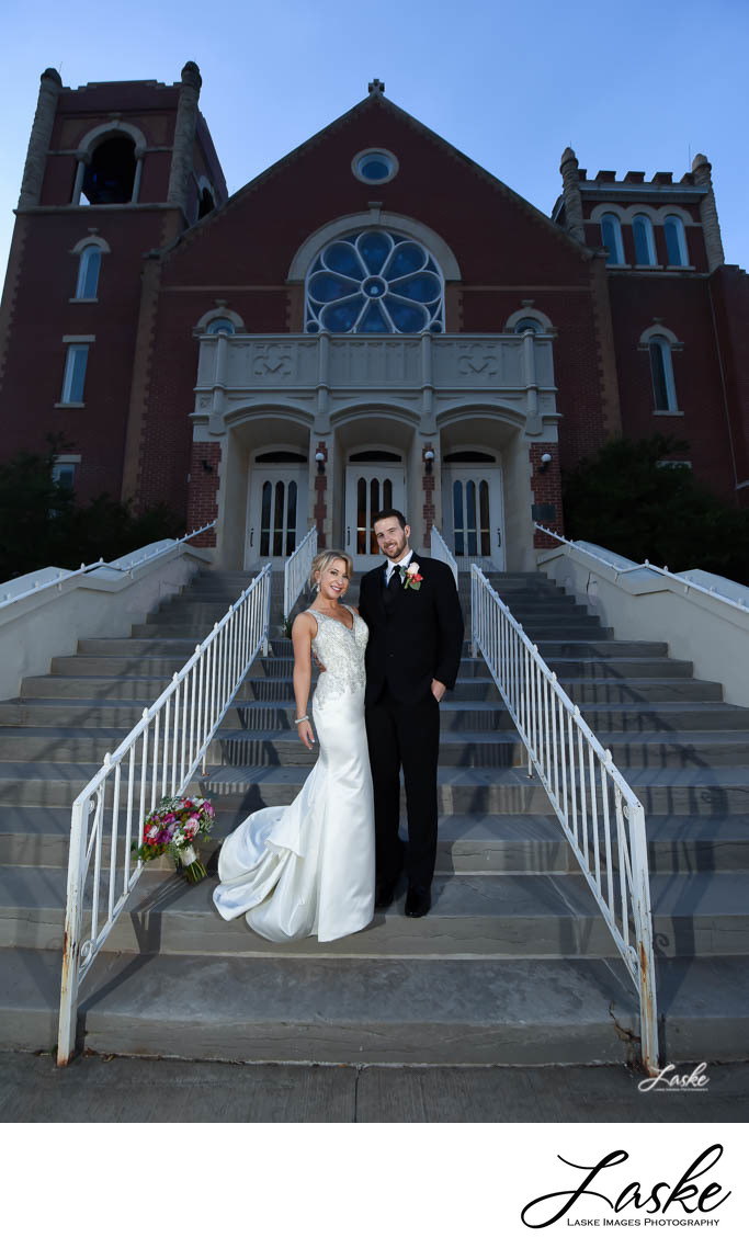 Bride and Groom stand on stairs outside the church on their wedding day