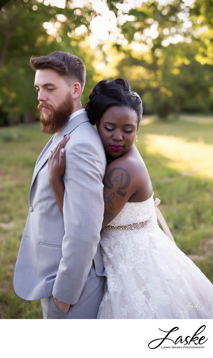 Bride Stands Behind Groom and Wraps Her Arms Around Him