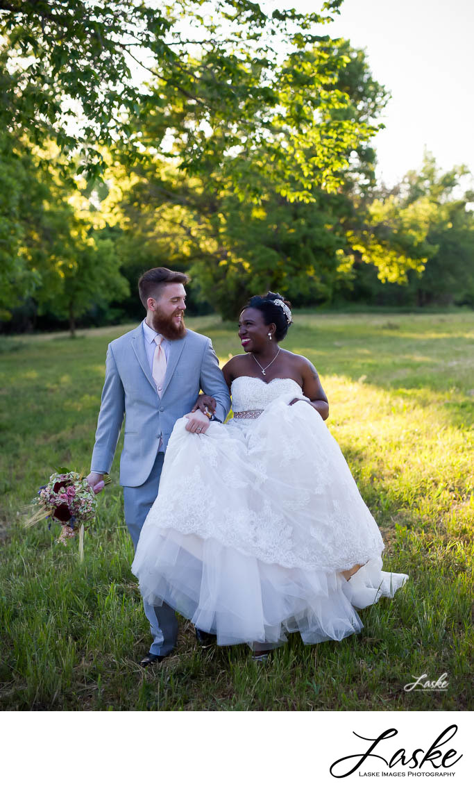 Bride and Groom Walk Across Field Laughing