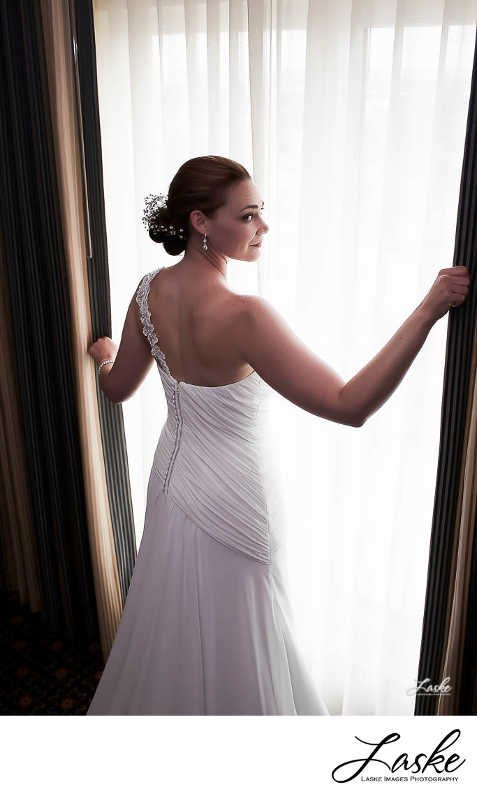 Bride Stands in Front of Window of Hotel