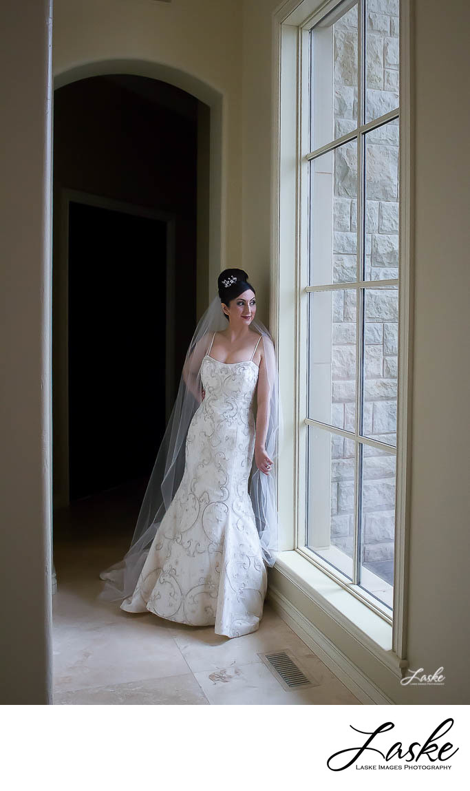 Bride Looks Out the Large Window on Her Wedding Day