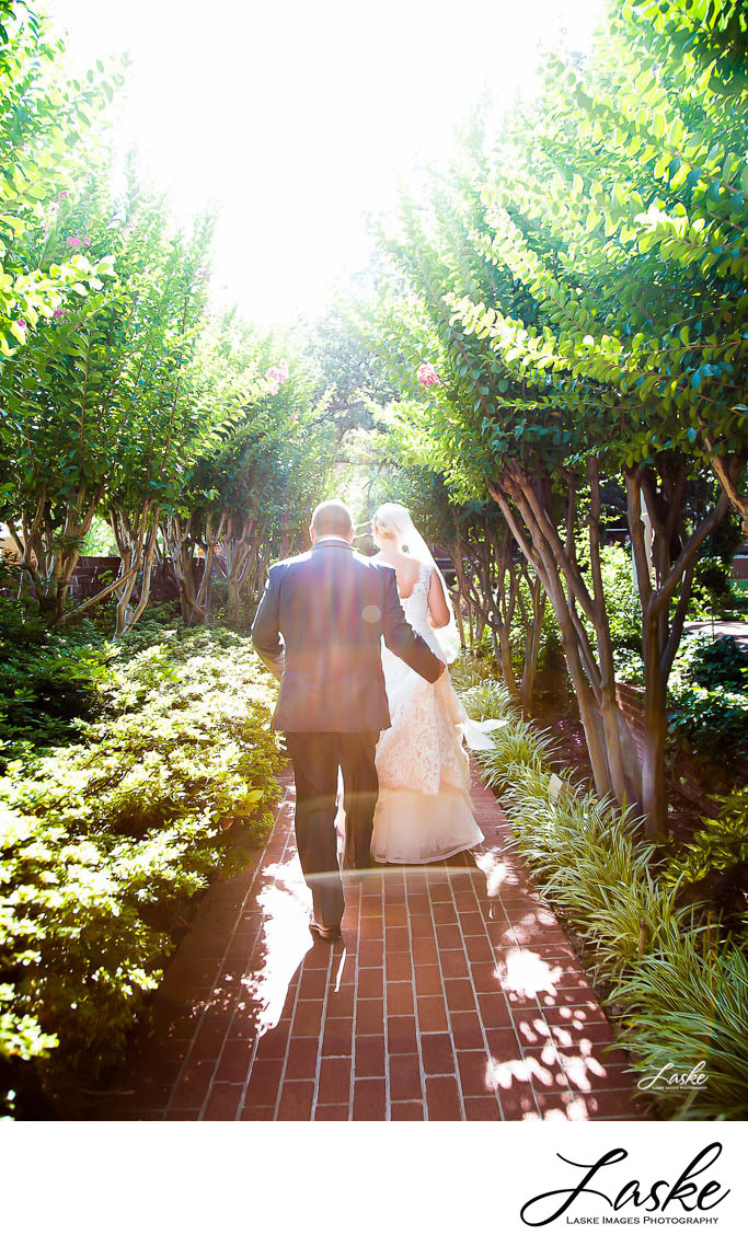 Couple Walks Along Brick Sidewalk in Garden