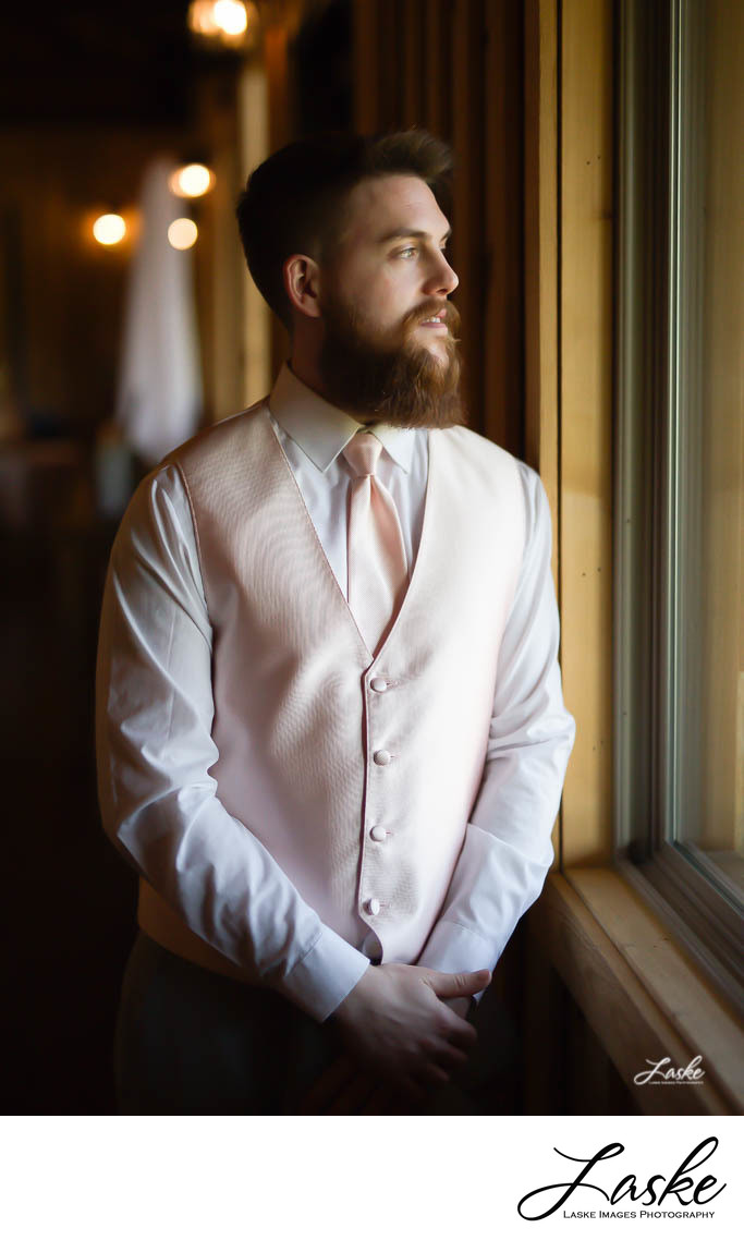 Groom stands and Looks Out Big Window