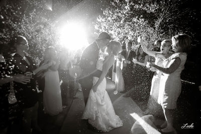 Bride and Groom Stop During their Exit to Lean In Close as Guests Cheer