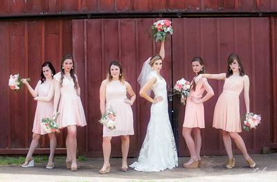 Bride And Bridesmaids Fun Pose Outside Barn Country Wedding