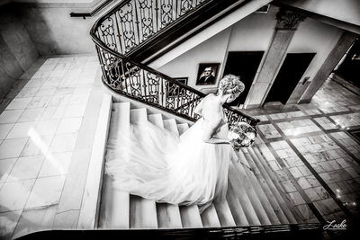 OKC Wedding Photographers Bride Runs Down the Stairs in Wedding Gown Holding Bouquet