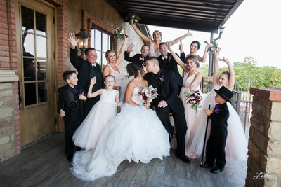 Bride and Groom Kiss as Wedding Party Cheers