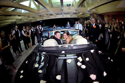 Bride and Groom in their black convertible getaway car, surrounded by guests as they leave the wedding. Rose petals rest on the back of the car.